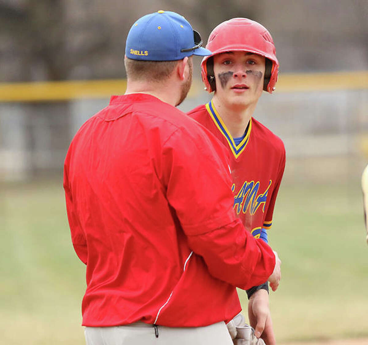 Roxana's Gavin Huffman (right) gets instructions from coach Jerry Wheaton after reaching third base in a 2019 game against EA-WR in Roxana. The Oilers and Shells were back on the field at Roxana Park on Friday, with Huffman pitching four near-perfect innings in a Roxana win.