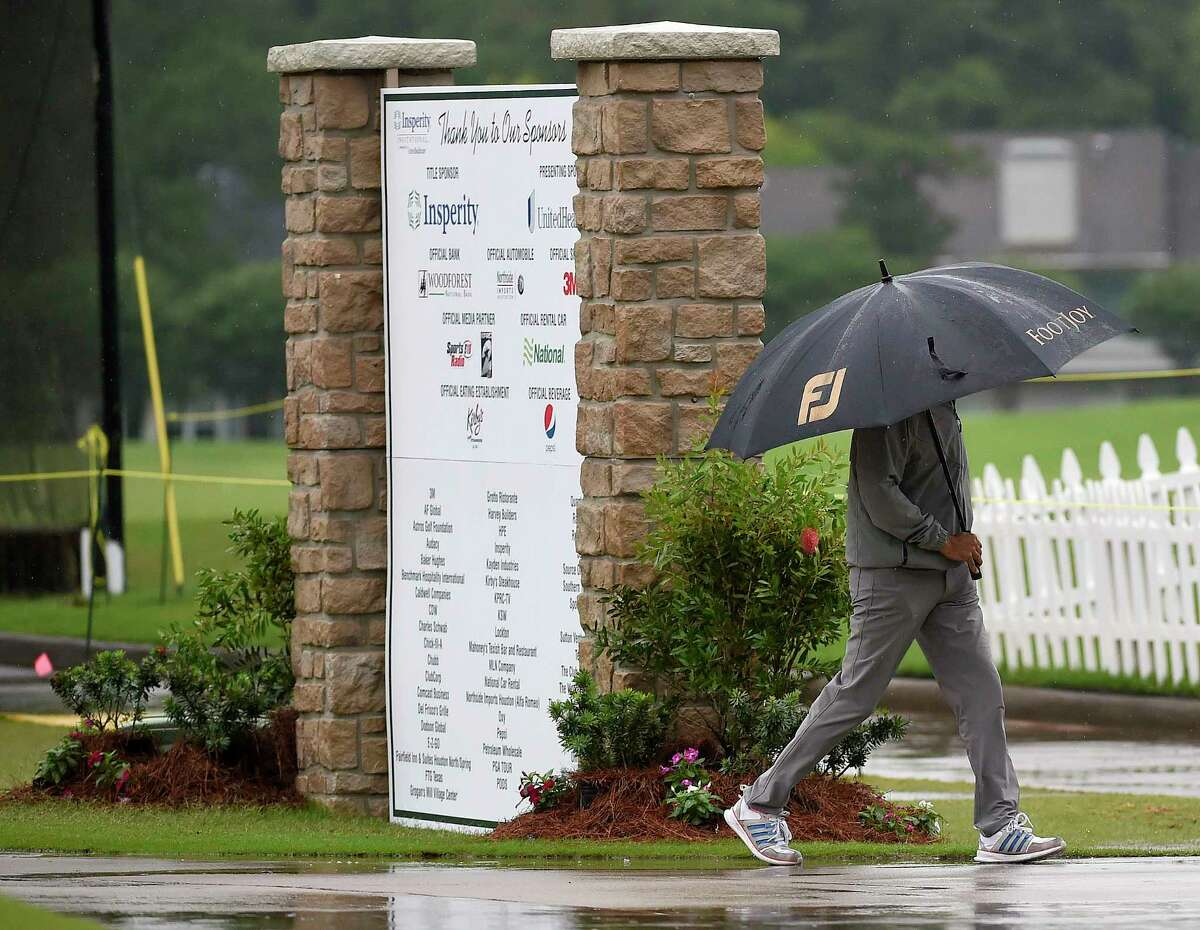 A volunteer walks past the practice tee during a weather delay before the first round of the Insperity Invitational golf tournament, Saturday, May 1, 2021, in The Woodlands, TX.