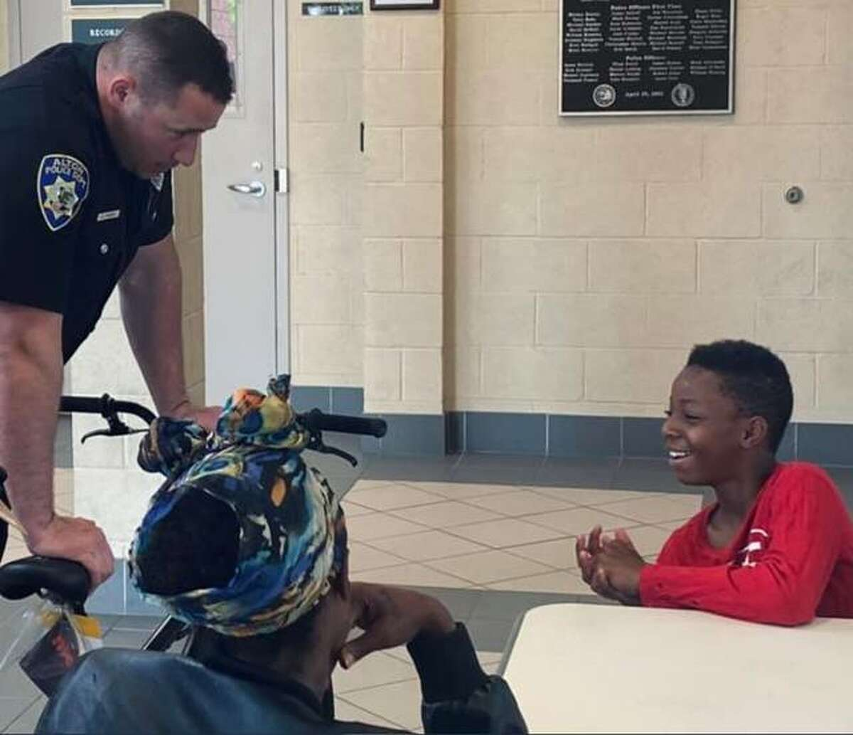 Keyondre Latham of Alton, far right, receives a new bicycle from the Alton Police Department. After Latham's bike was stolen while he was running an errand for his family, officers pitched in and bought him a new one.