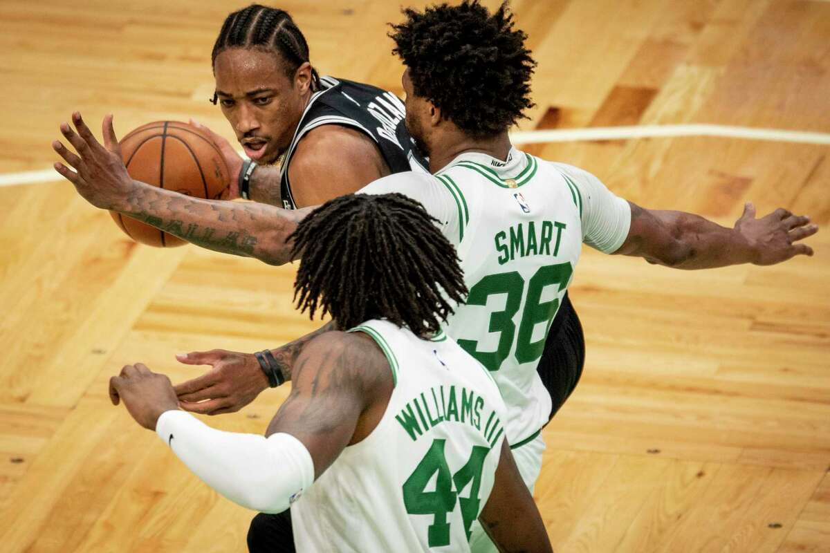 DeMar DeRozan, left, of the Spurs drives to the basket against Marucs Smart (36) of the Celtics at TD Garden on April 30, 2021 in Boston.