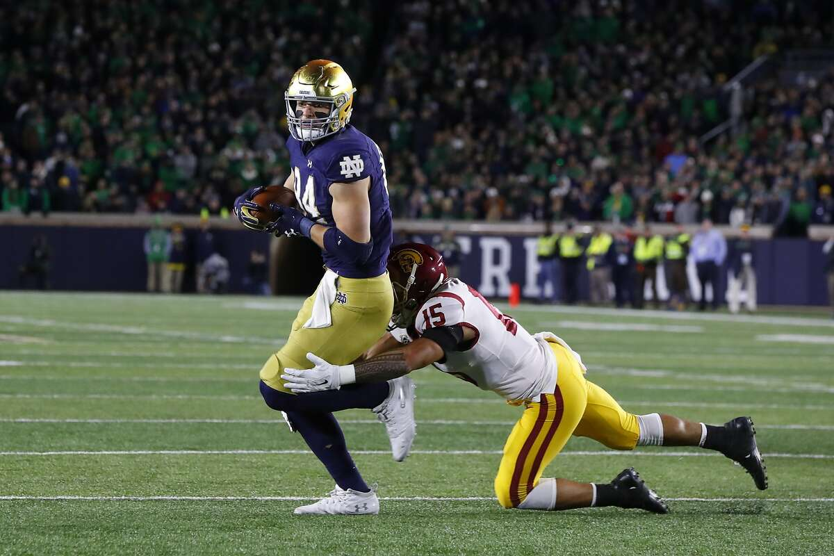 Notre Dame tight end Cole Kmet (84) breaks the tackle of Southern California safety Talanoa Hufanga (15) on his way to a touchdown in the first half of an NCAA college football game in South Bend, Ind., Saturday, Oct. 12, 2019. (AP Photo/Paul Sancya)