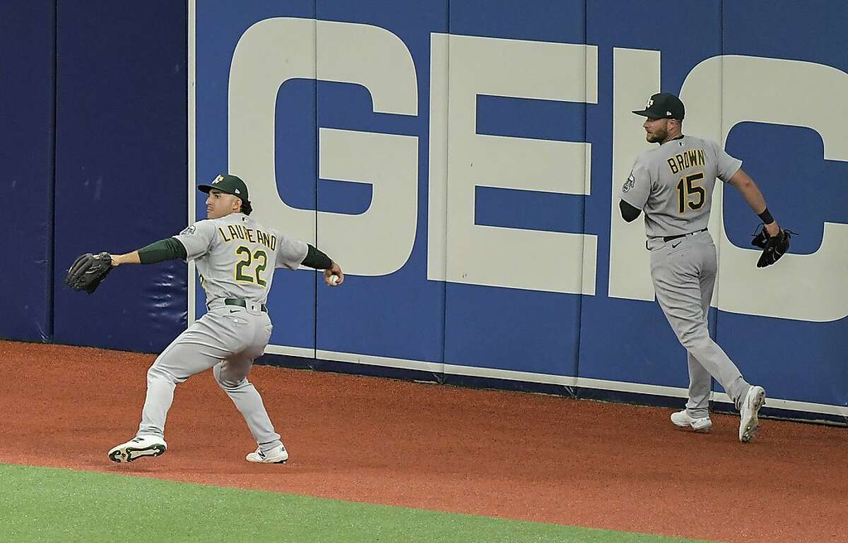 Oakland Athletics' Seth Brown (15) backs up Ramon Laureano (22), who throws the ball after fielding a double off the wall hit by Tampa Bay Rays' Manuel Margot during the first inning of a baseball game Wednesday, April 28, 2021, in St. Petersburg, Fla. (AP Photo/Steve Nesius)