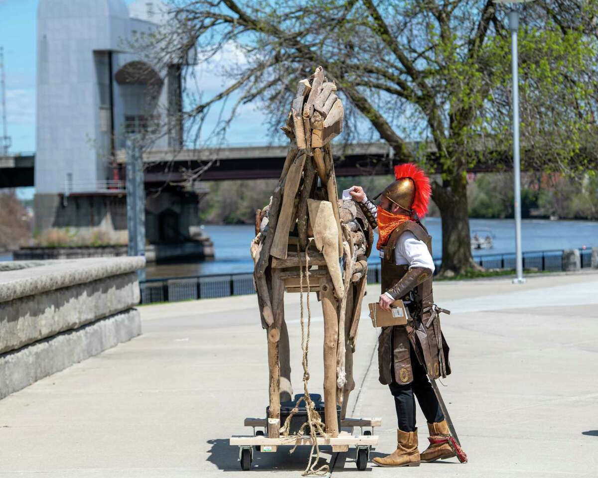 David Girard, the artistic director of the Troy Foundry Theatre, puts a note in a Trojan Horse at Riverfront Park in Troy on Saturday, May 1, 2021. The horse, made by Danny Killion of Weathered Wood, has a hollow belly to receive missives about people, events and feelings from 2020. (Jim Franco/Special to the Times Union)