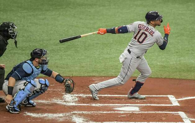 Home plate umpire Chad Fairchild, left, and Tampa Bay Rays catcher Mike Zunino, center, looks on as Houston Astros' Yuli Gurriel hits a two-run single during the first inning of a baseball game Saturday, May 1, 2021, in St. Petersburg, Fla. (AP Photo/Steve Nesius) Photo: Steve Nesius, Associated Press / Copyright 2021 The Associated Press. All rights reserved