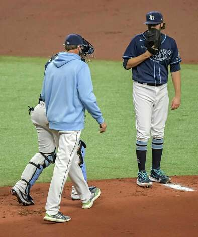 Tampa Bay Rays pitching coach Kyle Snyder, center, and catcher Mike Zunino walk to the mound to talk with starter Josh Fleming, right, after back-to-back walks against the Houston Astros during the first inning of a baseball game Saturday, May 1, 2021, in St. Petersburg, Fla. (AP Photo/Steve Nesius) Photo: Steve Nesius, Associated Press / Copyright 2021 The Associated Press. All rights reserved