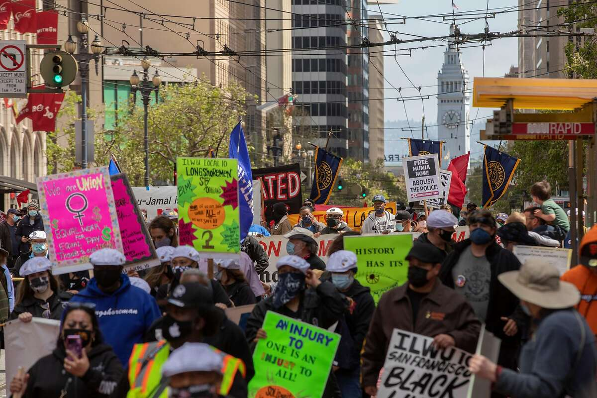 A crowd marches up Market Street to support worker rights.