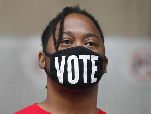 """Norman Harris wears a face mask that reads """"vote"""" during the Protect Our Vote rally, Saturday, May 1, 2021, in Conroe. Demonstrators spoke out against House Bill 6 and Senate Bill 7, which puts limits on how and when voters can cast their ballots. Photo: Jason Fochtman/Staff Photographer / 2021 © Houston Chronicle"""