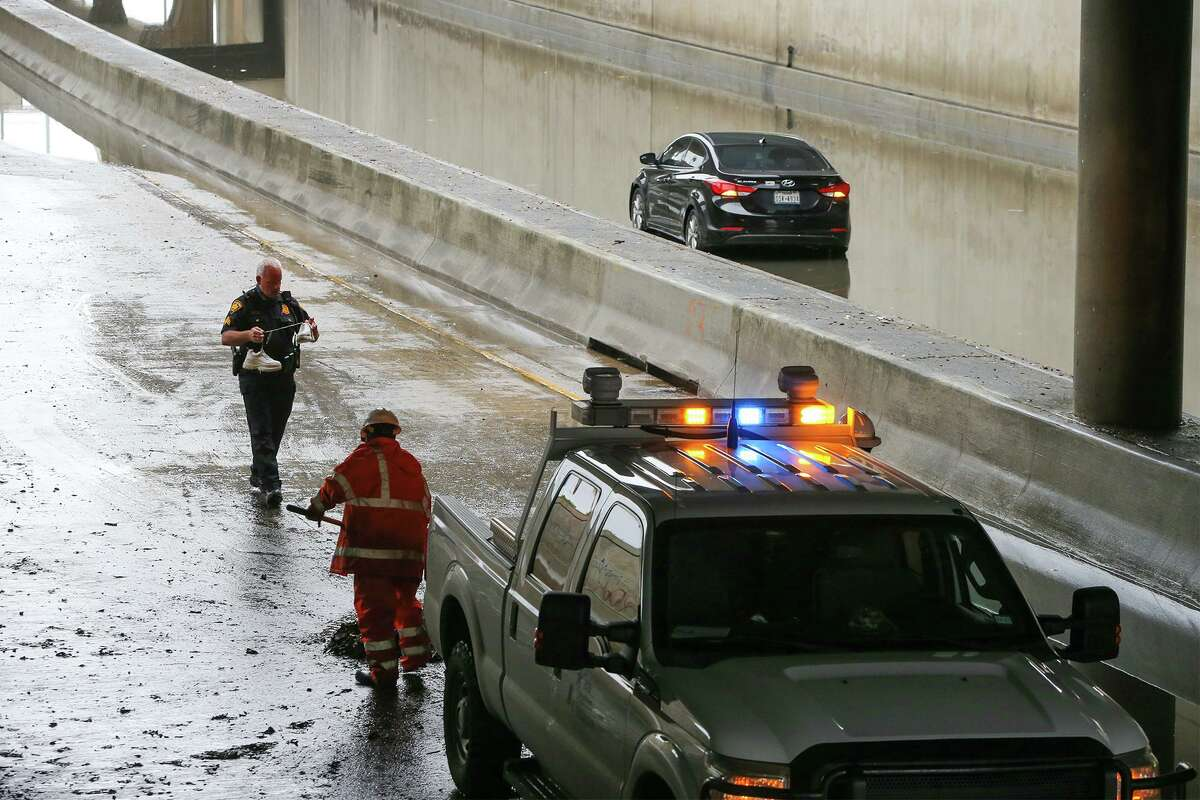 A San Antonio police officer takes a pair of sneakers he found to Texas Department of Transportation workers shoveling mud off I-35 under San Pedro Avenue on Saturday, May 1, 2021.