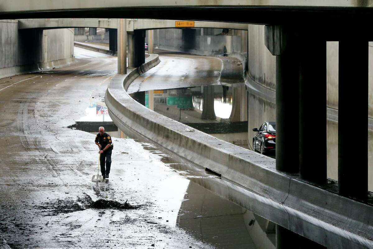 A San Antonio police officer shovels mud off Interstate 35 under San Pedro Avenue on Saturday, May 1, 2021. The highway had to be closed because of flooding from heavy rains in the area.