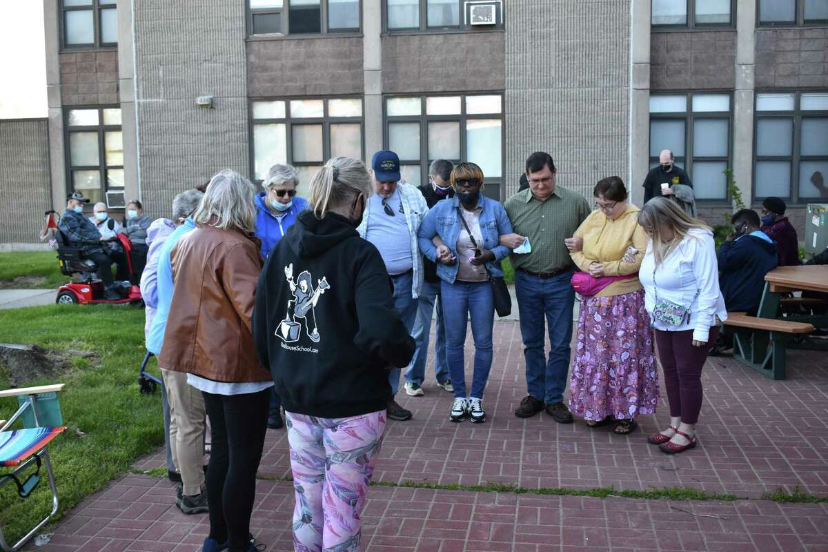Residents of the Surfside apartments gathered Saturday to discuss new security measures after a 74-year-old woman was allegedly sexually assaulted there earlier in the week. Here, Gloria McCalot leads the group in prayer.
