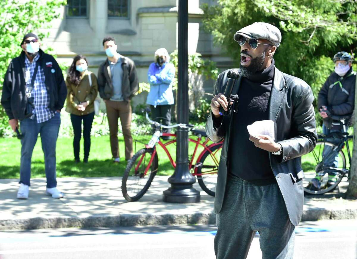 """New Haven, Connecticut - Saturday, May 01, 2021: Davarian L. Baldwin, the Paul E. Raether Distinguished Professor of American Studies at Trinity College in Hartford, Connecticut, and the author of """"In the Shadow of the Ivory Tower: How Universities are Plundering our Cities"""" speaks during a protest in front of Yale President Salovey's office on and people gathered to paint a sign on Prospect Street next to the Yale University Campus """"YALE: RESPECT NEW HAVEN"""" that includes a a visual representation of Yale University's $31 billion endowment compared to its voluntary contribution to the city of New Haven, encouraging Yale to """"pay its far share"""" of the burden of operating the city."""