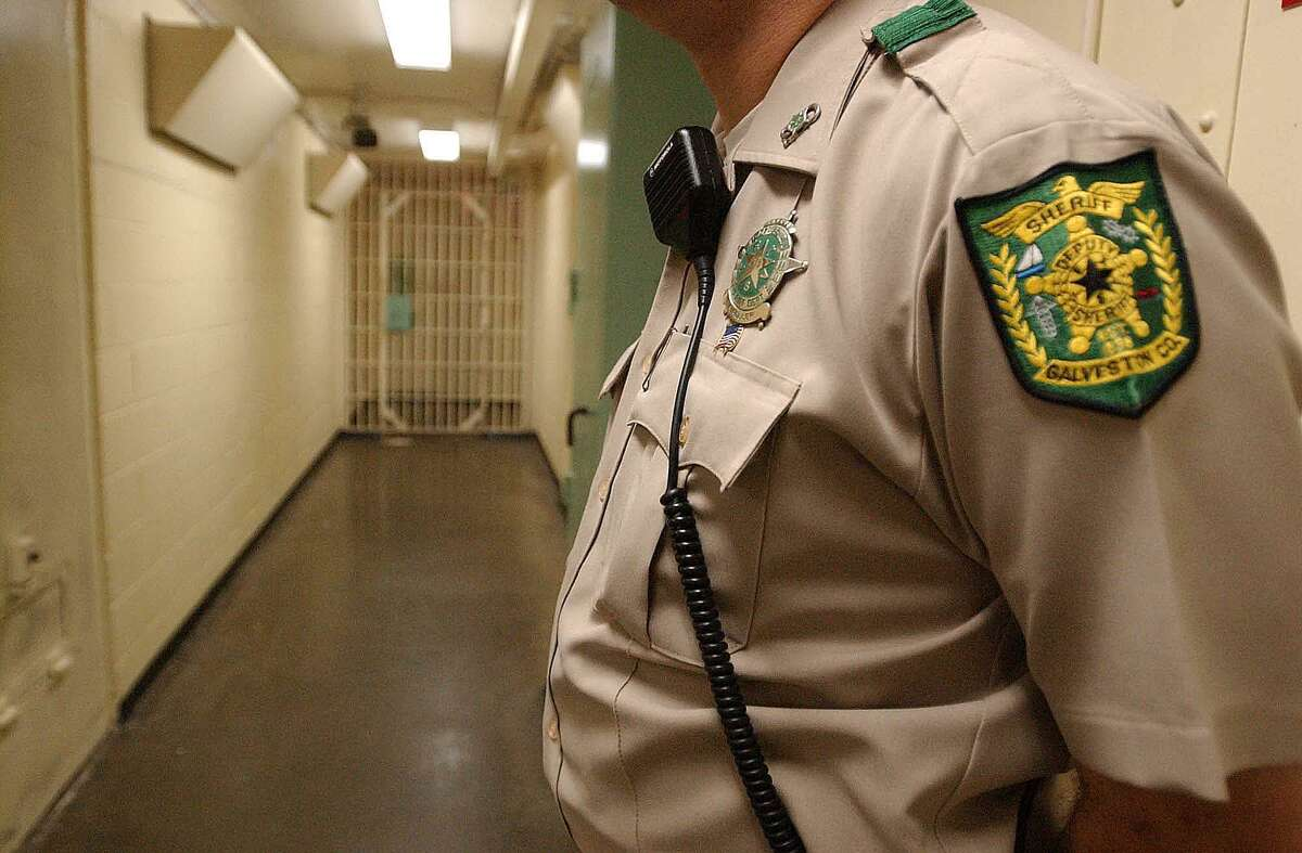 A file photo pictures a deputy standing guard with his radio attached to his collar at the Galveston County Jail.