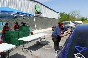 Joyce Moreno, right, with Be A Champion Inc., works with others, including volunteers from The Tree Mount Temple Church, to hand out food for children in front of the church at 6035 Seguin Road last month.