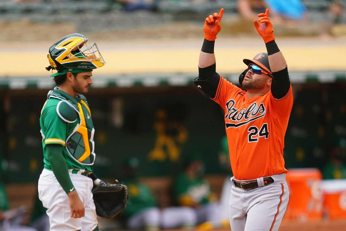 Baltimore's DJ Stewart celebrates his two-run home run during the sixth inning at the Coliseum as A's catcher Aramis Garcia regroups. It was the Orioles' only extra-base hit of the game.