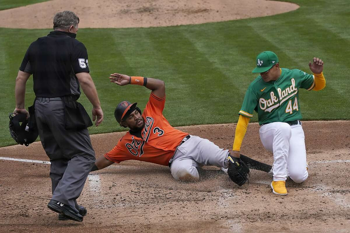 Umpire Greg Gibson, left, watches as Baltimore Orioles' Maikel Franco (3) slides home to score against Oakland Athletics pitcher Jesus Luzardo (44) during the third inning of a baseball game in Oakland, Calif., Saturday, May 1, 2021. (AP Photo/Jeff Chiu)