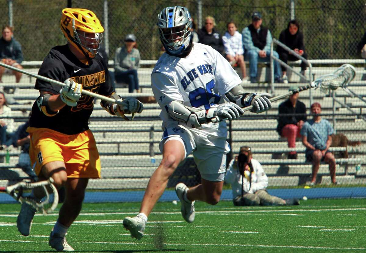 Darien's Braeden Pokorny (99) manuevers past Brunswick's Charlie Johnson (27) to score a goal during boys lacrosse action in Darien, Conn., on Saturday May 1, 2021.