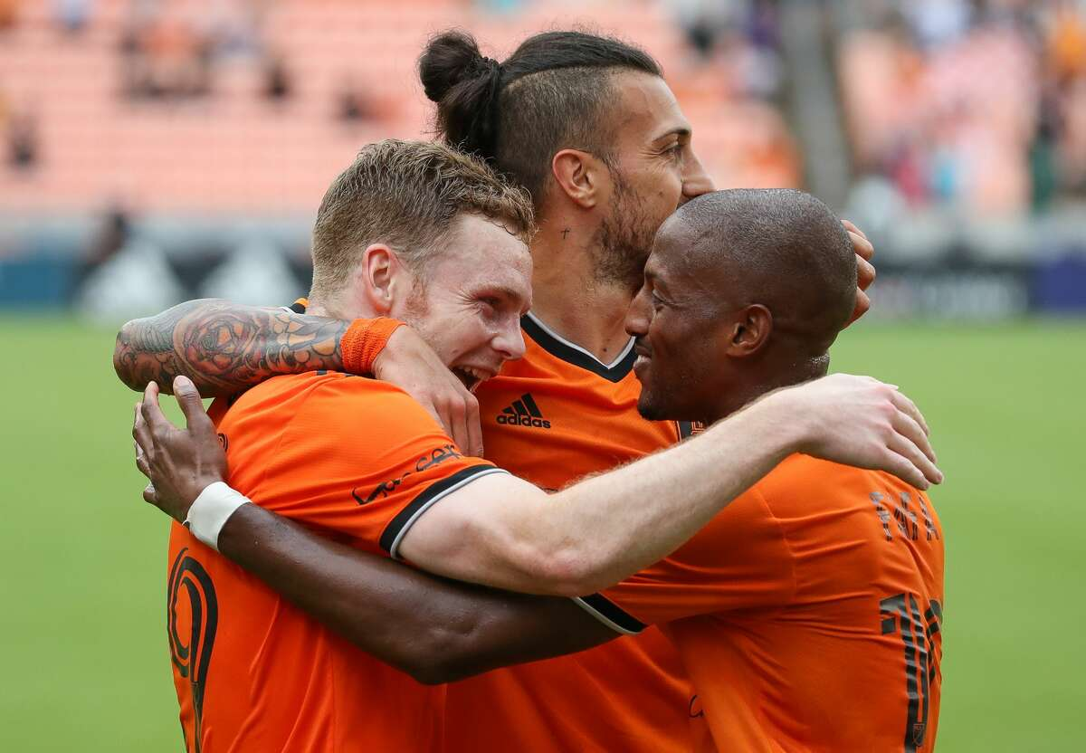 Houston Dynamo FC forward Tyler Pasher (19), left, celebrates with fellow forwards Maximiliano Urruti (37) and Fafa Picault (10) after scoring the tying goal against the Los Angeles FC during the second half of an MLS match at BBVA Stadium on Saturday, May 1, 2021, in Houston. The game ended 1-1.