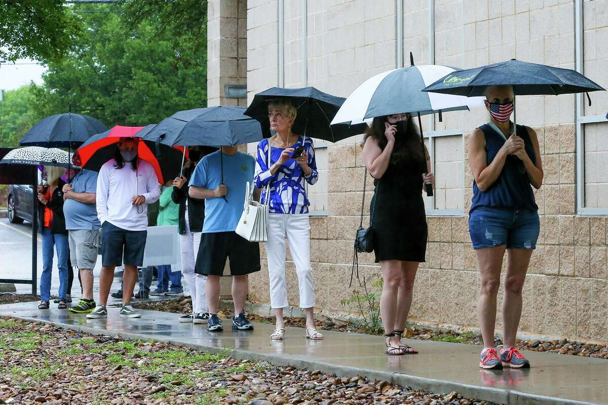 People wait in line in the rain to cast their votes in the May 2021 election at Brook Hollow Library, 530 Heimer Road, on Saturday, May 1, 2021.
