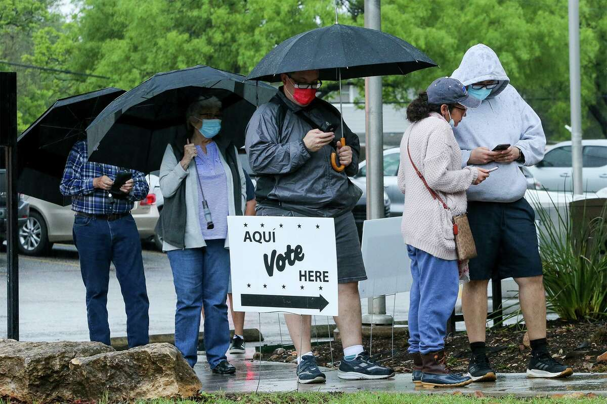 People wait in line in the rain to cast their votes in the May 2021 election at Brookhollow Library, 530 Heimer Rd., on Saturday, May 1, 2021.