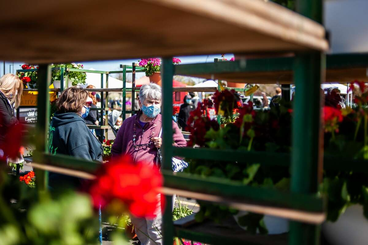 File Photo :: Jean Scoles browses through flowers during opening day of the Midland Area Farmers Market, May 1, 2021.