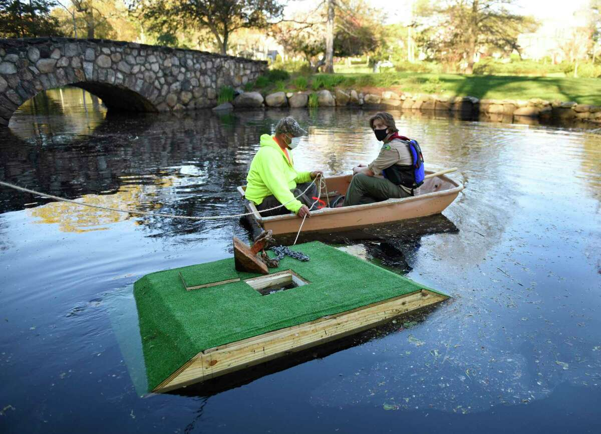 Greenwich High sophomore William van Rhyn, right, and park foreman Jonathan Fasone set up a turtle sanctuary at Binney Park Pond in Old Greenwich, Conn. Monday, April 26, 2021. For his Eagle Scout service project, Van Rhyn constructed two floating boards lined with turf to provide a habitat for turtles in the pond at Binney Park in cooperation with the town.