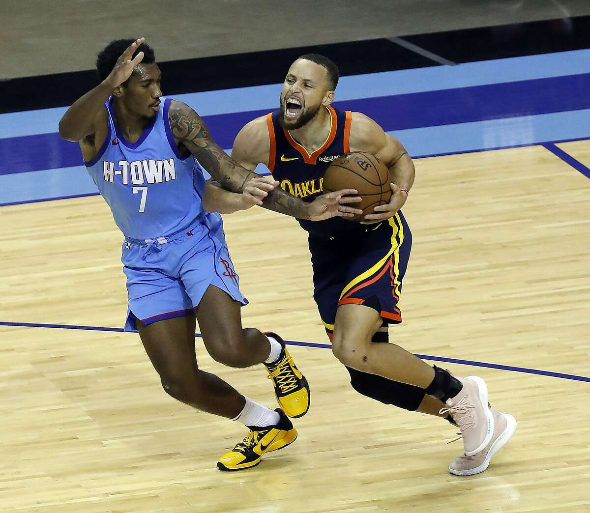 Houston's Armoni Brooks tries to keep his hand in while guarding a driving Stephen Curry.