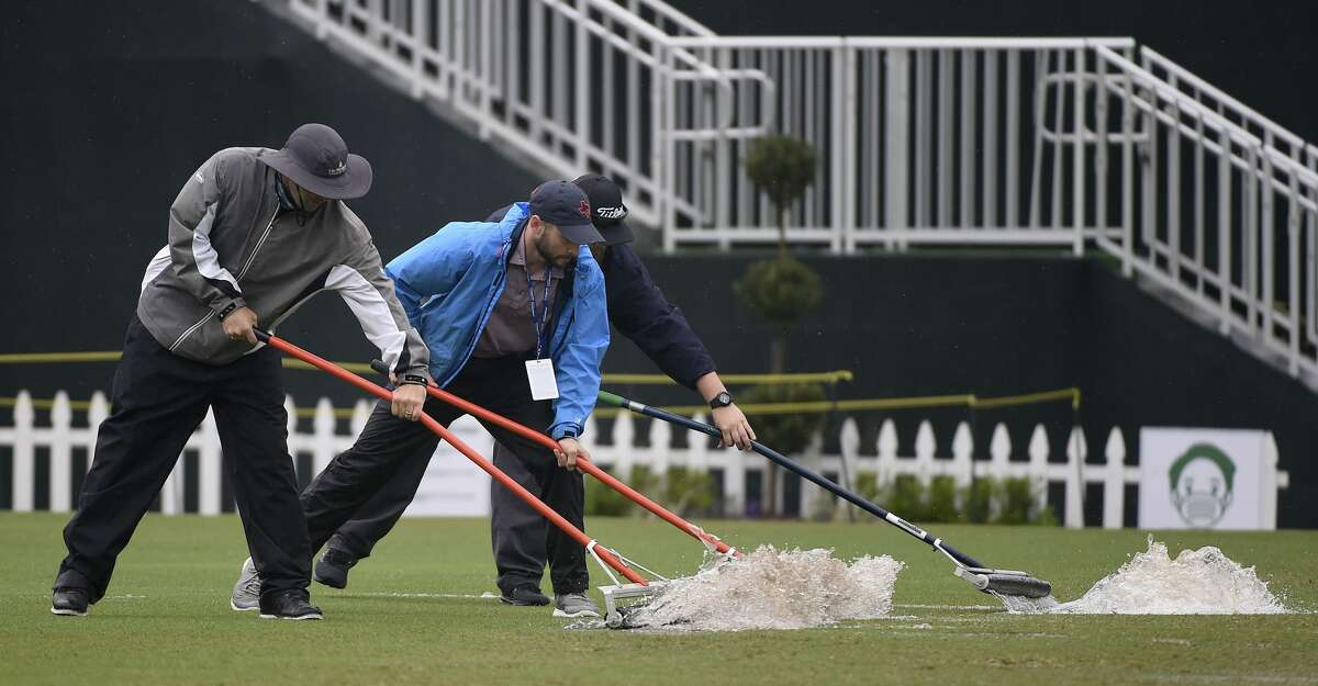 Workers push water off the driving range during a weather delay before the first round of the Insperity Invitational golf tournament, Saturday, May 1, 2021, in The Woodlands, TX.
