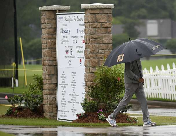A volunteer walks past the practice tee during a weather delay before the first round of the Insperity Invitational golf tournament, Saturday, May 1, 2021, in The Woodlands, TX. Photo: Eric Christian Smith/Contributor