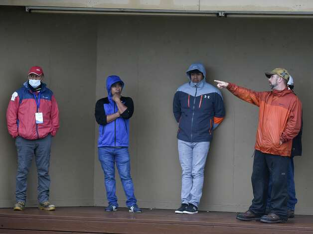 Woodlands Tournament Course grounds crew take shelter under a scoring area during a weather delay before the first round of the Insperity Invitational golf tournament, Saturday, May 1, 2021, in The Woodlands, TX. Photo: Eric Christian Smith/Contributor