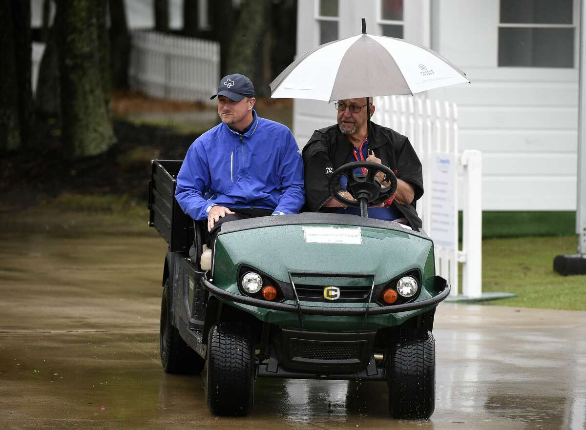 Volunteers drive near the practice tee during a weather delay before the first round of the Insperity Invitational golf tournament, Saturday, May 1, 2021, in The Woodlands, TX.