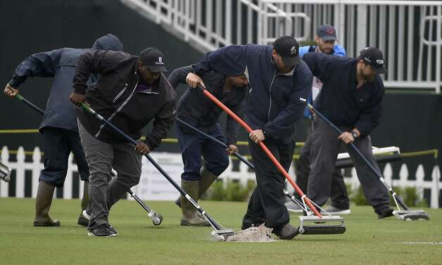 Workers push water off the driving range during a weather delay before the first round of the Insperity Invitational golf tournament, Saturday, May 1, 2021, in The Woodlands, TX. Photo: Eric Christian Smith/Contributor