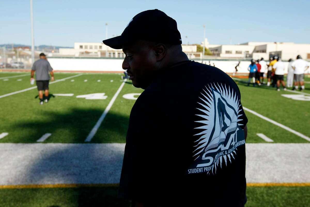 Head Coach Michael Peters talks to fellow coaching staff while the team are being addressed by another member of the coaching staff during football practice at Mcclymonds high school on Monday, August 05, 2013 in Oakland, Calif.