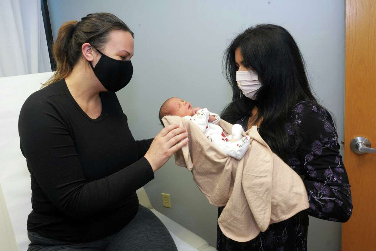 Julianna Diaz, left, and her daughter Olivia Rose meet Dr. Ronika Choudhary, right, in her office in Trumbull, Conn. April 30, 2021. Olivia Rose was born last Monday.