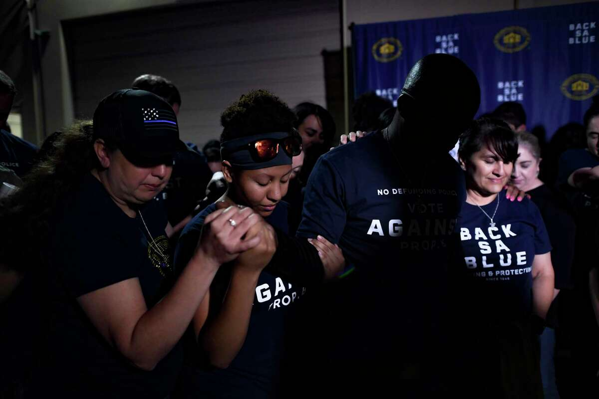 People pray after the defeat of Proposition B, the ballot initiative that would have repealed the police union's right to collectively bargain, on May 1. 2021, election.