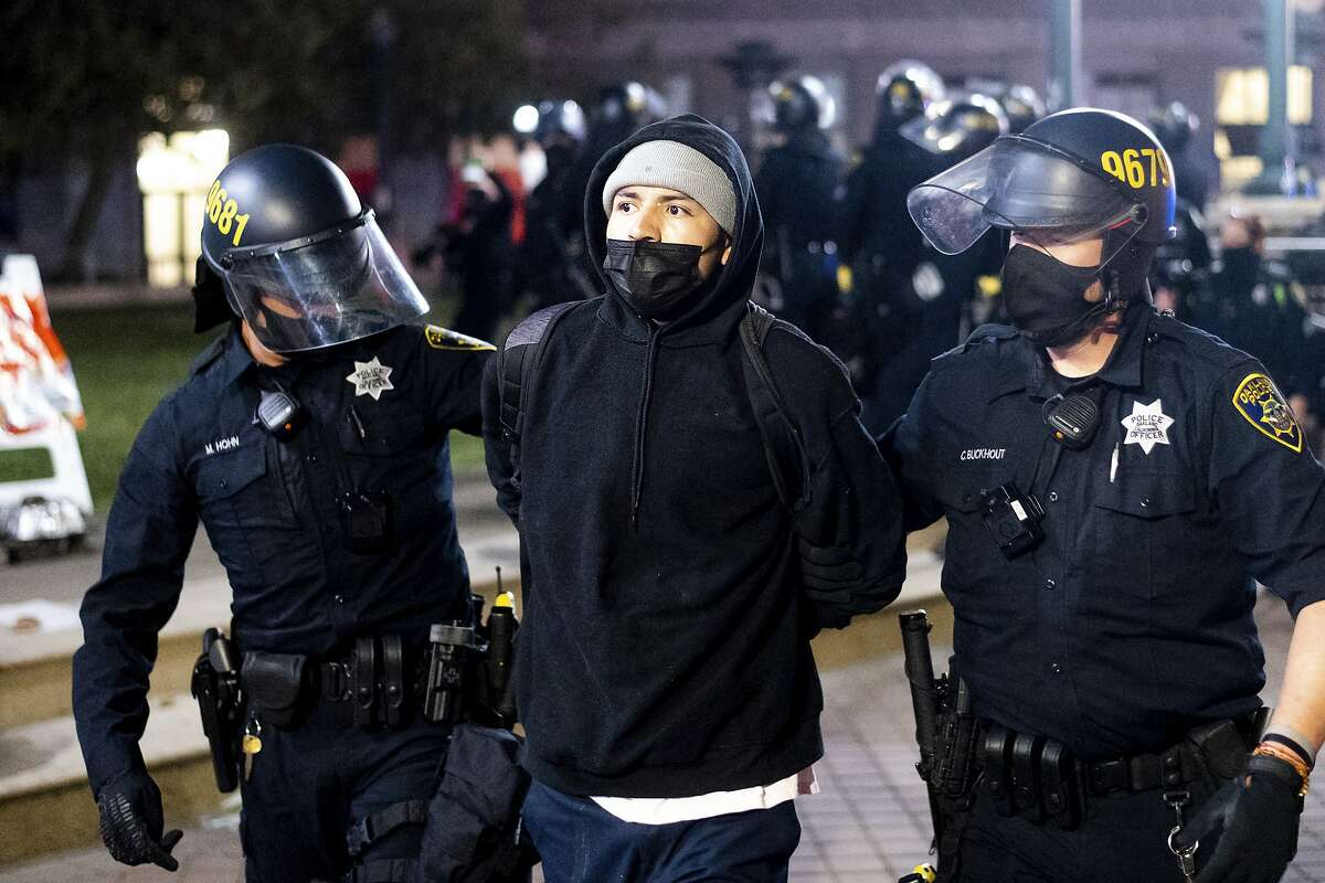 Police officers detain an anti-police demonstrator during a march through Oakland.