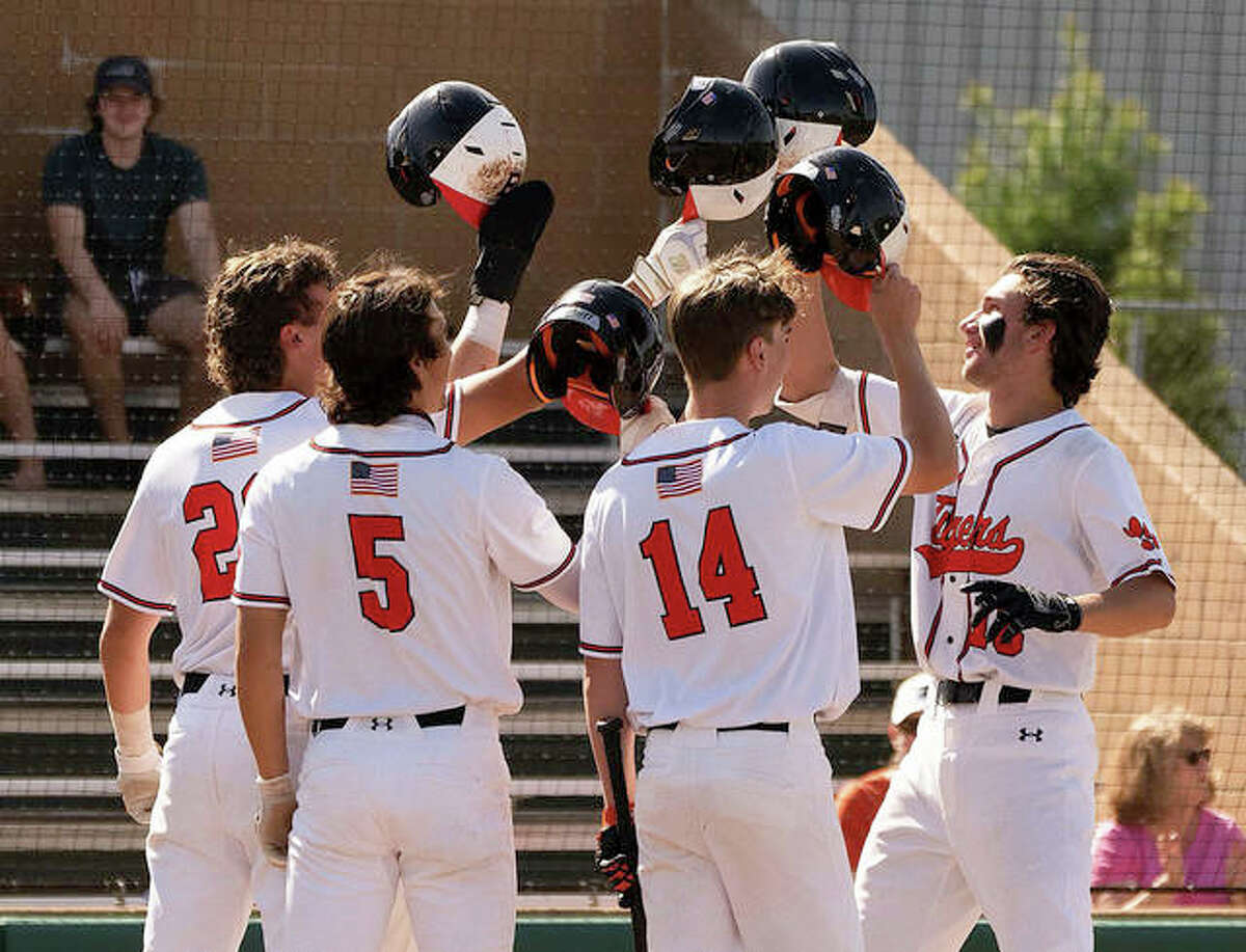 Edwardsville first baseman Riley Iffrig, right, celebrates with teammates after hitting a grand slam against Saint Louis University High on Saturday at Tom Pile Field in Edwardsville.