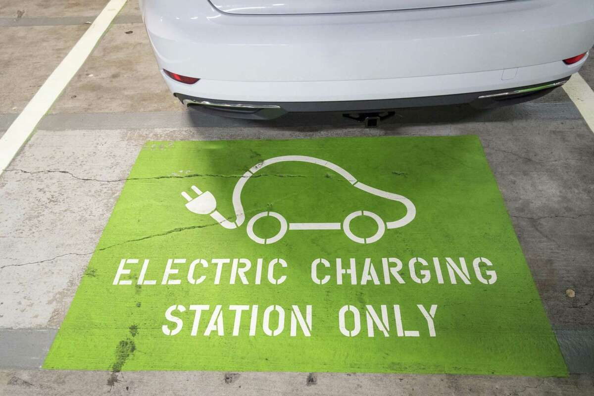 """An """"Electric Charging Station Only"""" sign is seen at a parking space in San Francisco on July 2, 2018."""