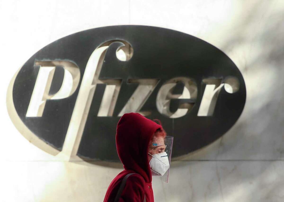 A woman wears a facemask as she walks by the Pfizer world headquarters in New York on November 9, 2020.