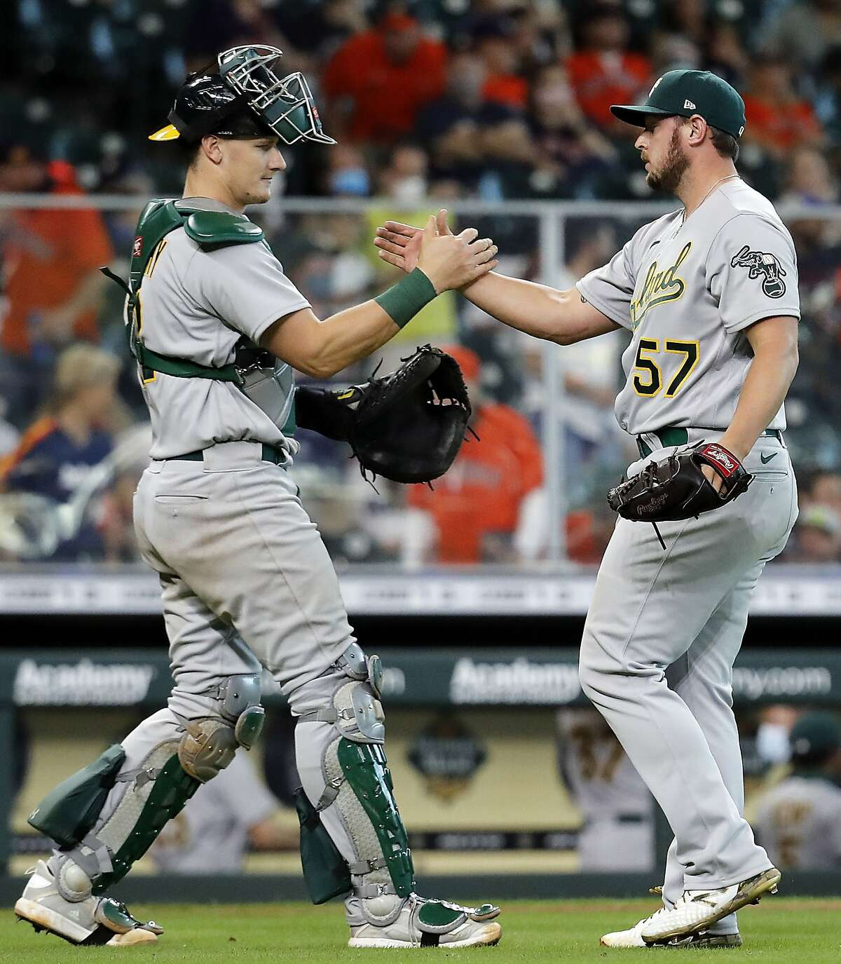 HOUSTON, TEXAS - APRIL 10: J.B. Wendelken #57 of the Oakland Athletics shakes hands with Sean Murphy #12 as they defeated the Houston Astros at Minute Maid Park on April 10, 2021 in Houston, Texas. (Photo by Bob Levey/Getty Images)
