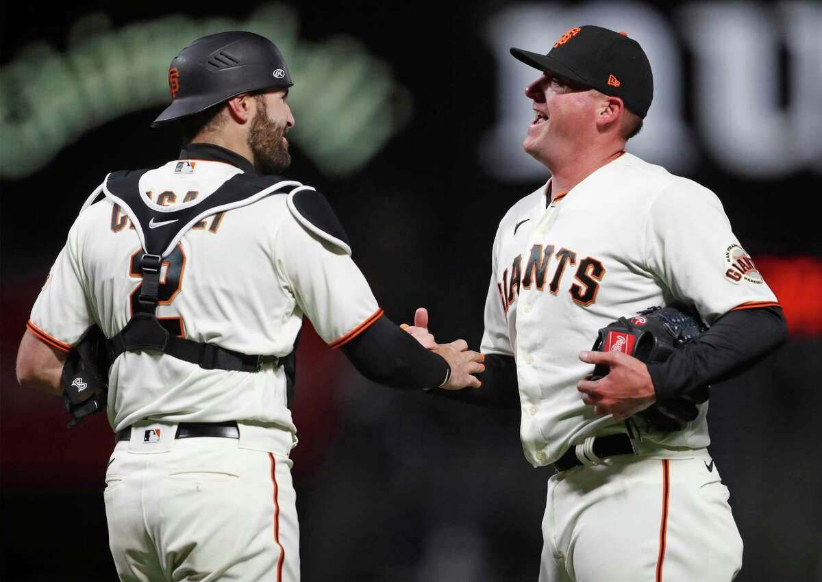 San Francisco Giants' reliever Jake McGee and catcher Curt Casali react after Giants' 3-0 win over Miami Marlins in MLB game at Oracle Park in San Francisco, Calif., on Thursday, April 22, 2021.