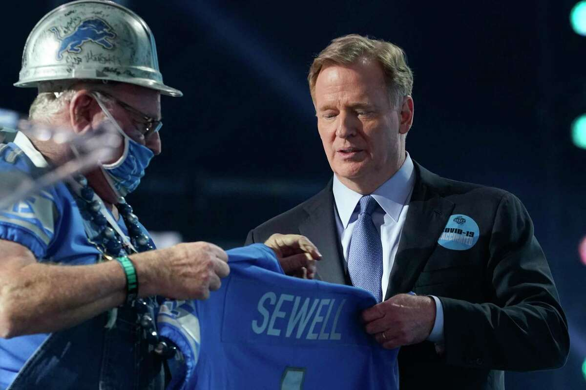 A Detroit Lions fan, left, who was chosen to be on stage, holds a team jersey with the name of the team's first-round pick Penei Sewell, an offensive lineman from Oregon, at the NFL football draft Thursday April 29, 2021, in Cleveland. (AP Photo/Tony Dejak)