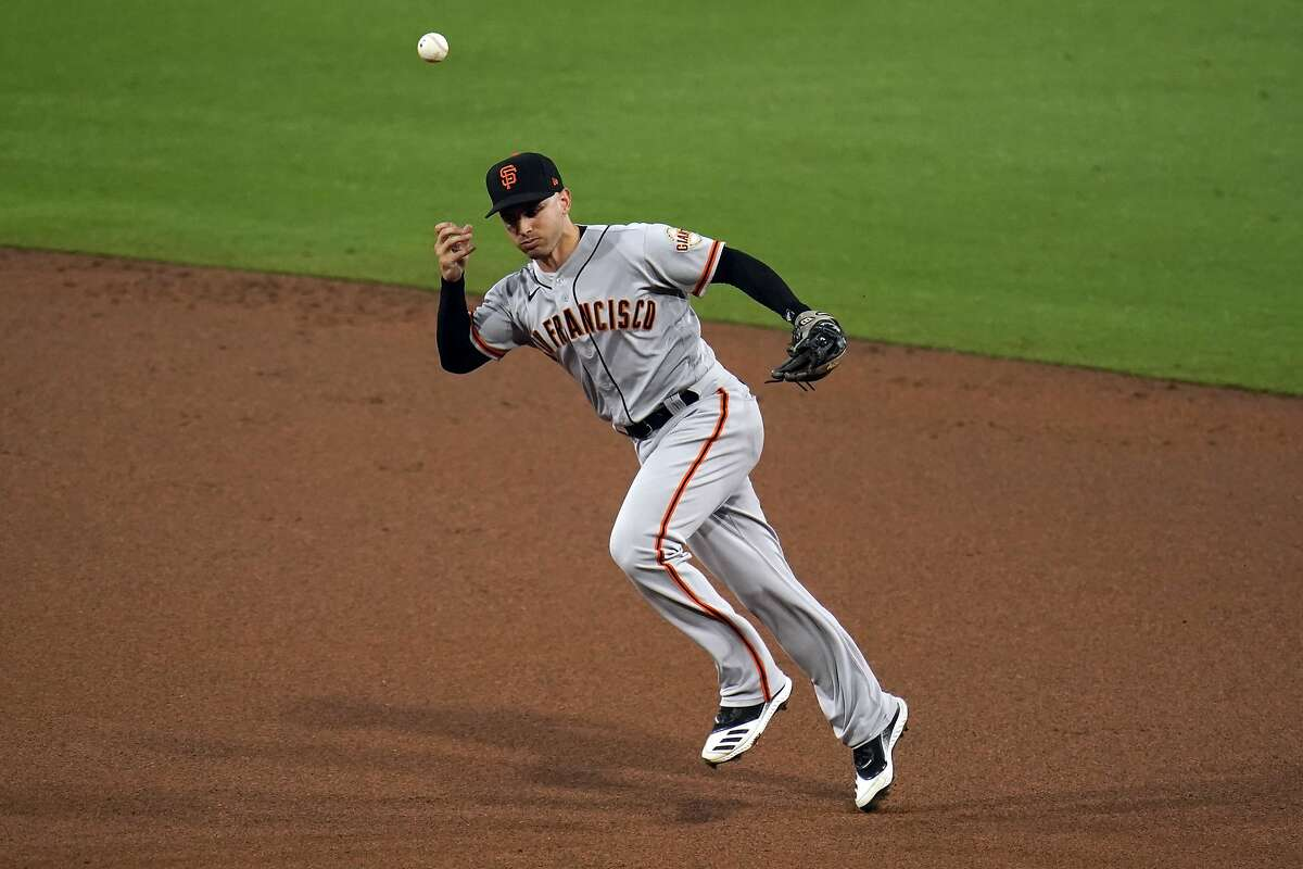 San Francisco Giants second baseman Tommy La Stella cannot field a ground ball hit for an RBI-single by San Diego Padres' Eric Hosmer during the first inning of a baseball game Friday, April 30, 2021, in San Diego. Padres' Trent Grisham scored on the play. (AP Photo/Gregory Bull)