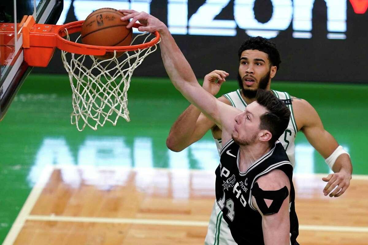 Spurs forward Drew Eubanks (14) dunks against Celtics forward Jayson Tatum during the first quarter of an NBA basketball game Friday, April 30, 2021, in Boston.