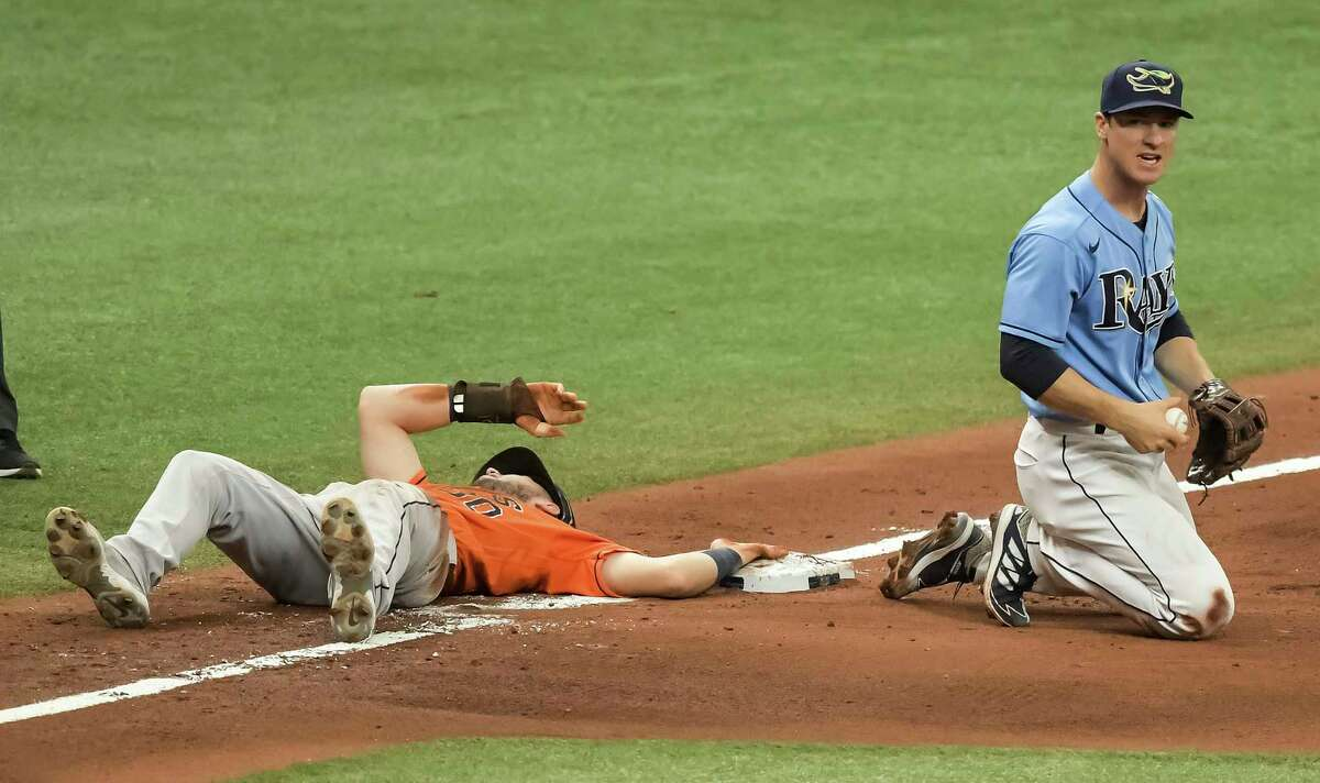 Tampa Bay Rays' Joey Wendle, right, holds the ball after Houston Astros' Kyle Tucker, left, beat the tag at third base on a throw from Rays center fielder Kevin Kiermaier during the sixth inning of a baseball game Sunday, May 2, 2021, in St. Petersburg, Fla. (AP Photo/Steve Nesius)