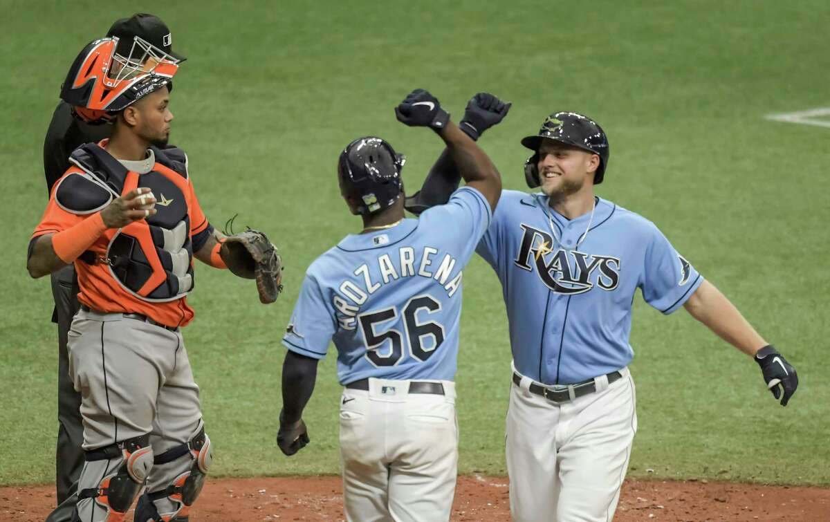 Houston Astros catcher Martin Maldonado, left, looks away as Tampa Bay Rays' Randy Arozarena (56) and Austin Meadows, right, celebrate Meadow's three-run home run during the fifth inning of a baseball game Sunday, May 2, 2021, in St. Petersburg, Fla. (AP Photo/Steve Nesius)