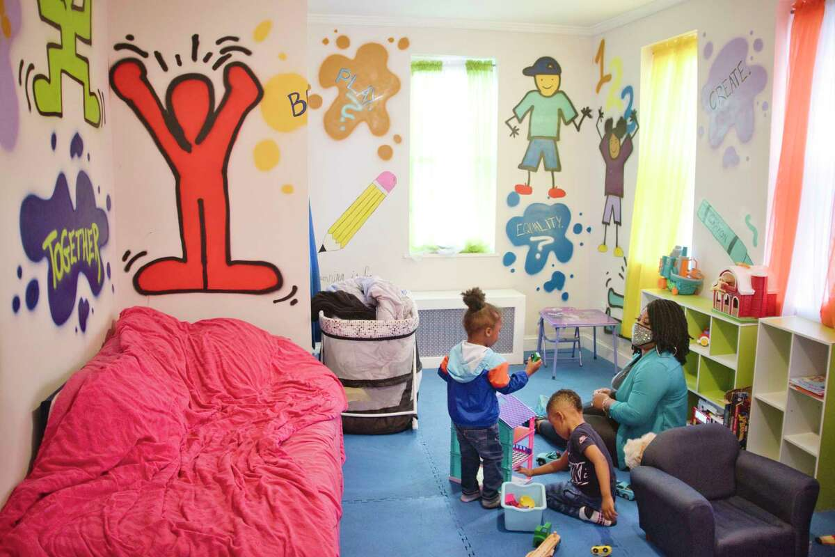 Analisa Sanchez spends time with Atreus, 2, left, and Damion, 4, at her daycare on Thursday, April 29, 2021, in Schenectady, N.Y. Sanchez started her daycare business in late August of 2020 and is in desperate need of federal help to cover costs, as are most day care providers in the wake of the pandemic. (Paul Buckowski/Times Union)
