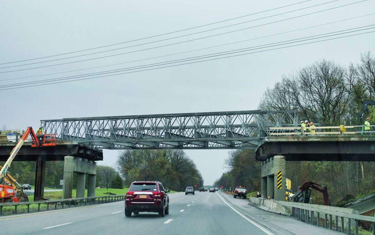 Work continues on the Sitterly Road overpass above Interstate 87 on Sunday, May 2, 2021, in Clifton Park, N.Y. Weeks ago a truck towing a trailer with a boom lift and traveling south on I-87 struck the overpass damaging it. (Paul Buckowski/Times Union)