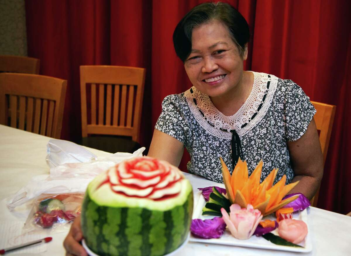 Jiraporn Namarsa is shown with decorative Thai food. She has shown customers at the Thai Topaz restaurant in Castle Hills how she creates decorative desserts with a small paring knife.