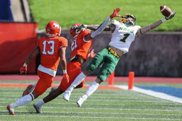 North Dakota State wide receiver Christian Watson (1) leaps past Sam Houston State defensive backs Isaiah Downes (13) Kameryn Alexander (21) for a first down reception during the fourth quarter of a quarterfinal game in the NCAA FCS football playoffs on Sunday, May 2, 2021, in Huntsville. Sam Houston advanced to the semifinals with a 24-20 win. Photo: Brett Coomer, Staff Photographer / © 2021 Houston Chronicle