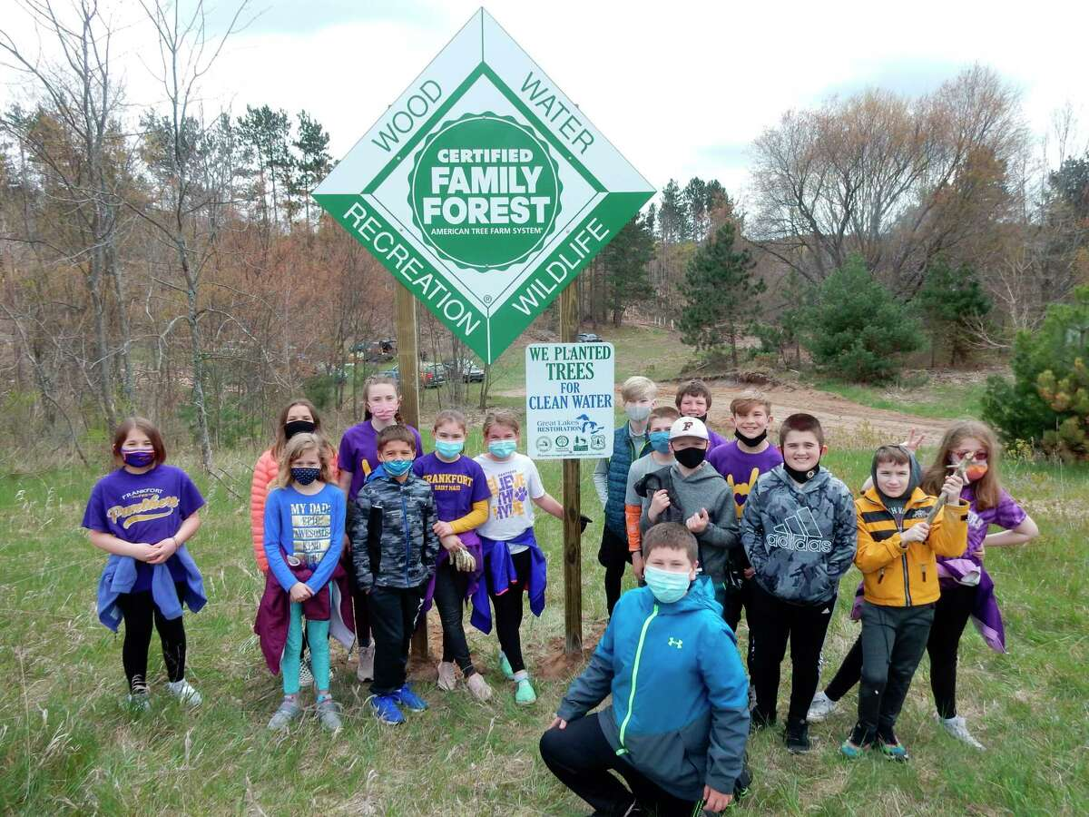 Students from Frankfort Elementary School pose with the sign from the Michigan Tree Farm Committee proclaiming Frankfort Elberta Schools' forest a certified Family Forest. (Courtesy Photo)